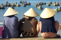 Three women in conical hats wait at the harbourside for the morning catch, Mui Ne, Vietnam.