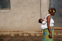 A pretty woman from Burundi carries her baby in the traditional African way. Beautiful simplicity.