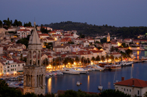 Evening lights on the island of Hvar, Croatia with yachts and sailboats docking for the night.