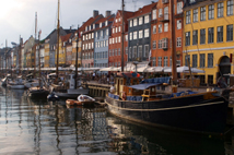 Boats moored along the Nihavn canal and restaurants under the colourful buildings.Copenhagen, Denmark.
