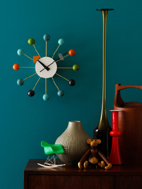 Various Mid Century home decor items photographed on teak side bar in a still life setting.